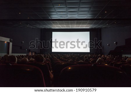 Empty cinema screen with audience. Ready for adding your picture. - stock photo