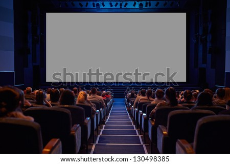 Empty cinema screen with audience. Ready for adding your picture. Screen has crisp borders. This shot was made using tripod with long exposure. - stock photo