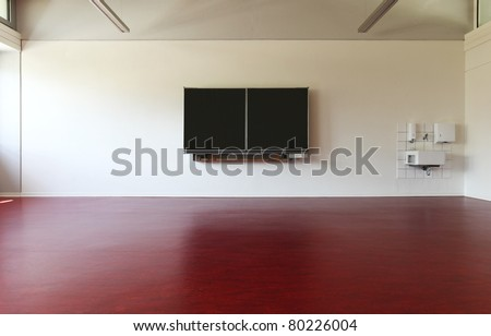 empty classroom with a red linoleum floor and blackboard