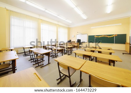 Empty classroom with wooden desks, chalk board and big windows in school. - stock photo