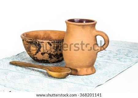 empty clay bowl, a mug and a wooden spoon - stock photo