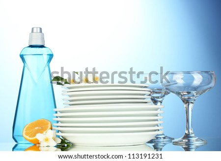 empty clean plates and glasses with dishwashing liquid, sponges and lemon on blue background - stock photo