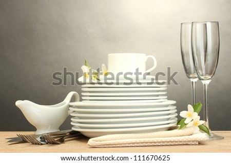 empty clean plates, glasses and cup on wooden table on grey background - stock photo