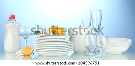 empty clean plates, glasses and cups with dishwashing liquidand lemon on blue background