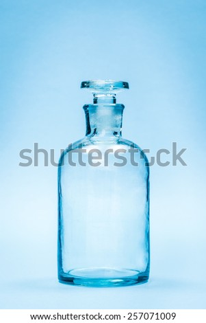Empty clear reagent bottle with glass stopper on blue background - stock photo