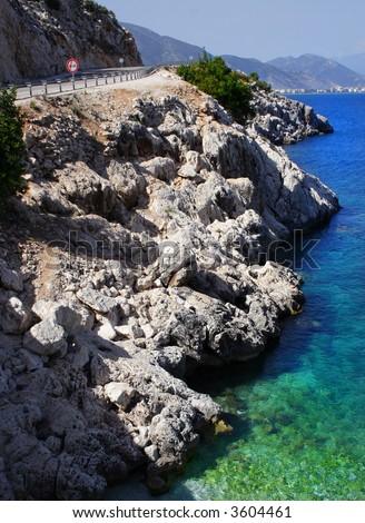 empty coastline road with a rocky shore - stock photo