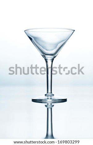 Empty cocktail glass on blue and white gradient background - stock photo