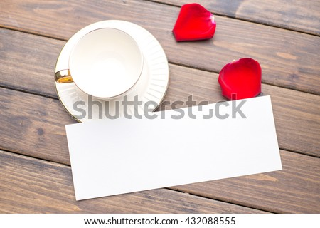 empty coffee cup and white blank paper on wood plank - stock photo