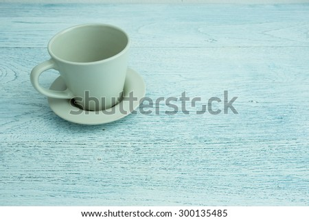 Empty coffee cup on old blue wooden table - stock photo