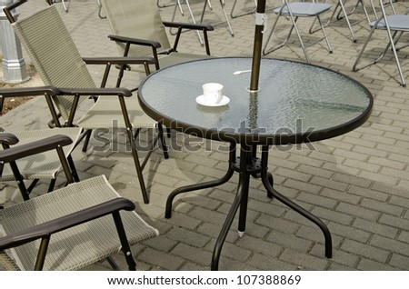 Empty coffee cup on table and chairs on pavement. Outdoor cafe.