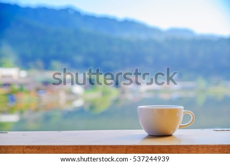 Empty coffee cup on wood table with blur background.