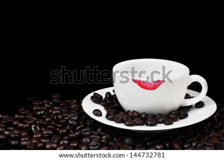 Empty Coffee cup with lipstick mark and beans on black background. - stock photo