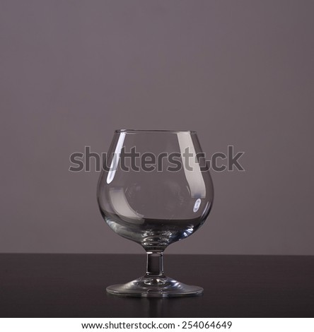Empty cognac glass with reflections on grey background - stock photo