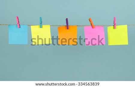 Empty colored paper notes hanging on a rope attached with pegs on a blue background - stock photo
