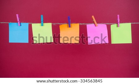 Empty colored paper notes hanging on a rope attached with pegs on a red background