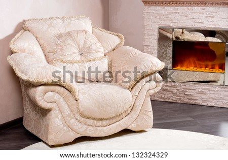 Empty comfortable elegant upholstered armchair in cream linen standing near a blazing fire insert in a living room