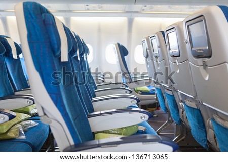 Empty comfortable seats in cabin of huge aircraft with screens in chairs back - stock photo