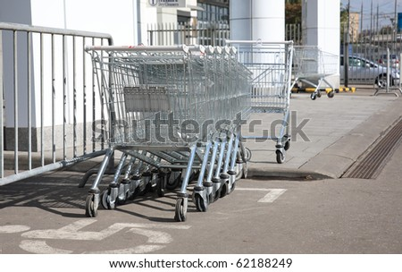 Empty commodity carts before an input in a supermarket - stock photo