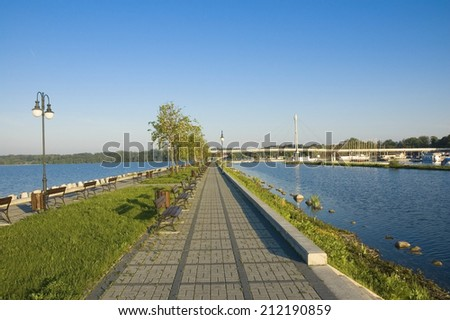 Empty concrete pier on the lakeshore and yachts moored in marina, Mazury, Poland - stock photo