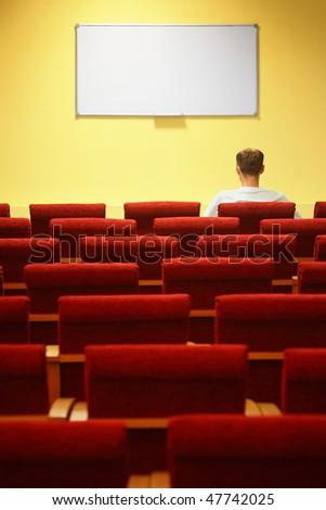 empty conference hall. rows of a chairs. focus on a first row. one man sitting in chair - stock photo