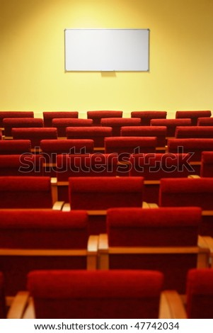 empty conference hall. rows of a chairs. focus on a screen - stock photo