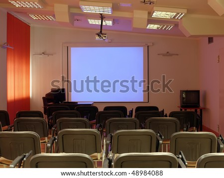 Empty conference room with blank projector screen