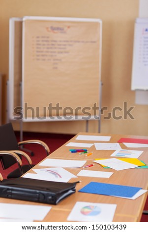 Empty conference table with notes scattered on top and a flipchart behind - stock photo