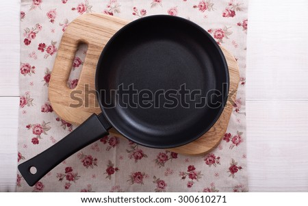 Empty cooking frying pan with tablecloth on white wooden background.  Flat mock up for design. Top view. - stock photo