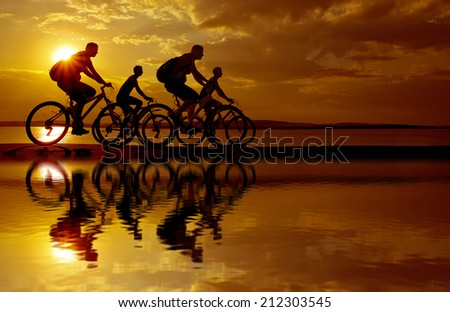 Empty Copy Space for inscription Image of sporty company friends on bicycles outdoors against sunset Silhouette four 4 cyclist going along shoreline coast Reflection sun on water - stock photo