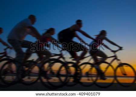 Empty Copy Space Sporty company friends on bicycles outdoors against sunset Silhouette five 5 cyclist going along shoreline coast Reflection sun on water Sport in Nature background Group of people - stock photo
