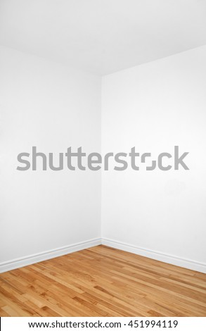 Empty corner of a renovated room with white walls and wooden floor.