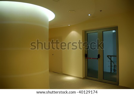 Empty corridor as seen in a modern office building - warm yellow tones and halogen lights - stock photo