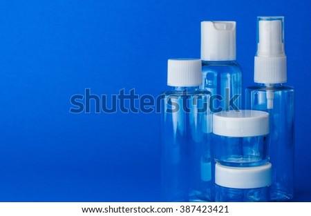 Empty cosmetic plastic transparent bottles on blue background - stock photo