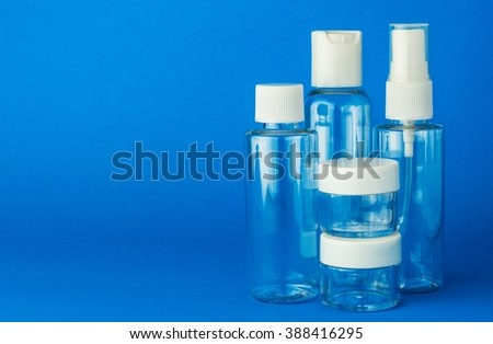 Empty cosmetic plastic transparent bottles on blue background, space for text - stock photo