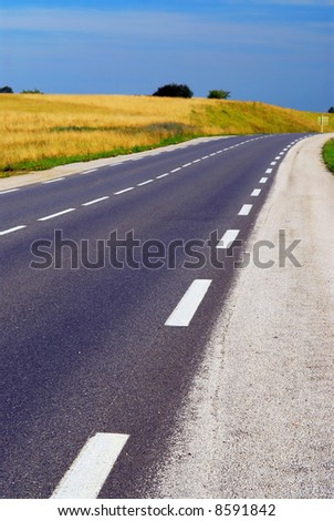 Empty country road among farm fields in rural France - stock photo
