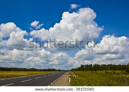 Empty Country Road and Blue Sky with White Clouds