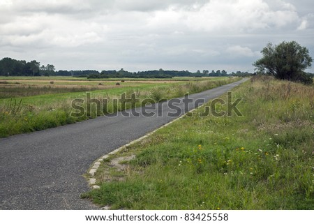 Empty country road at cloudy day - stock photo