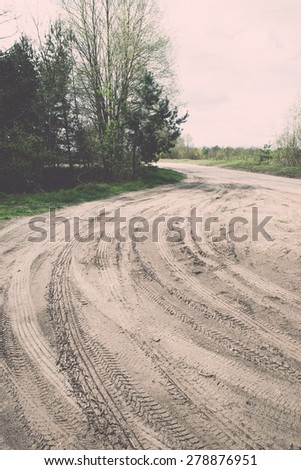 empty country road in spring with perspective and shadows - retro vintage grainy film look