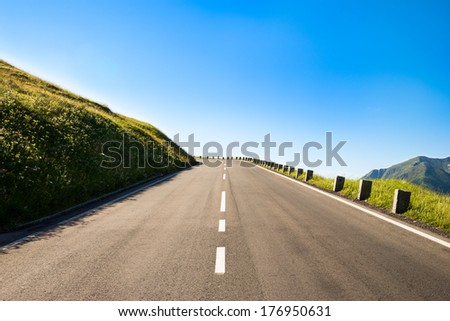 empty country road with a sharp left curve in the brow of a hill in the mountainous area - stock photo