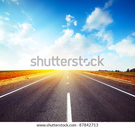 Empty countryside asphalt road and cloudy blue sky - stock photo