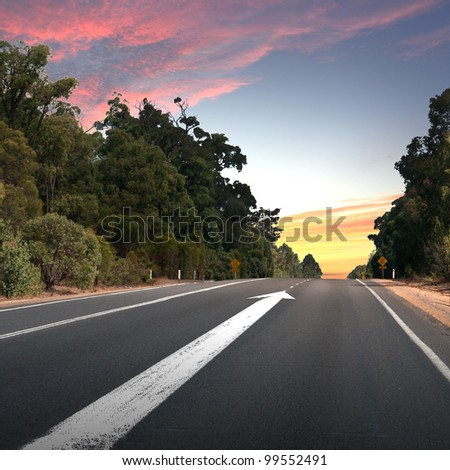 Empty countryside road with white arrow - stock photo