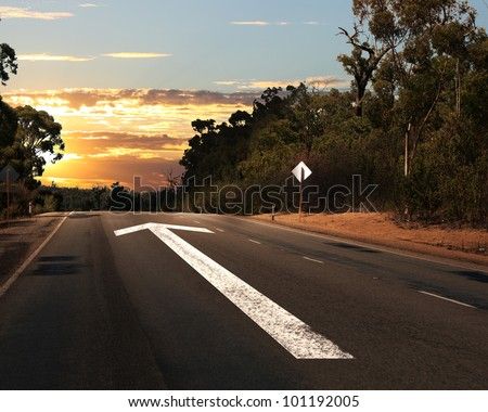 Empty countryside road with white arrow sing on it - stock photo