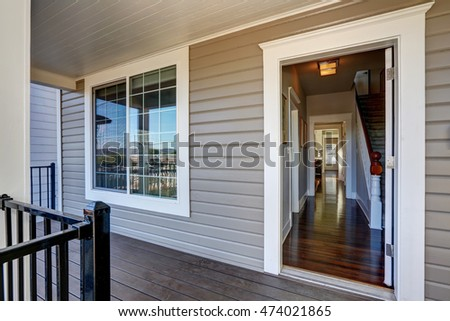 Empty covered porch with open front door and french window. Northwest, USA