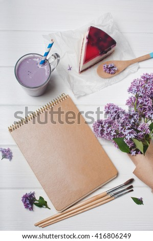 Empty craft cover of notebook with cup of bilberry milkshake, black current cheesecake slice, brushes and bouquet of lilac flowers on the white wooden background, copy space. Top view. - stock photo