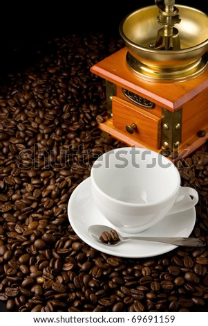 empty cup and gold grinder on coffee beans - stock photo