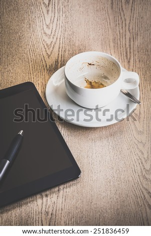 empty cup of coffee and tablet with stylus pen for business theme - stock photo