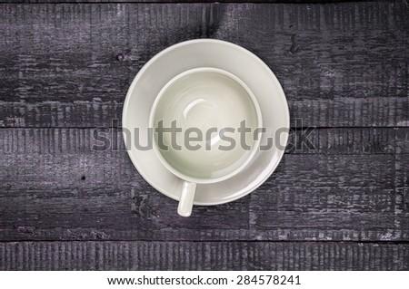 Empty cup with saucer on wooden background - stock photo