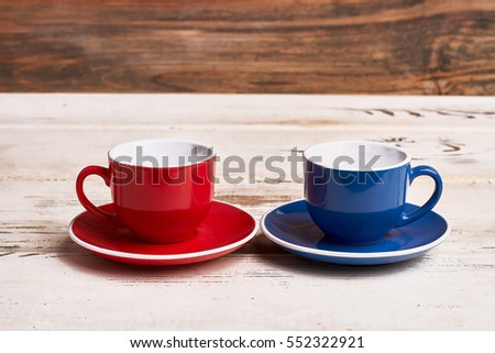 Empty cups on wooden background. Red and blue mugs. Invite friend for tea.