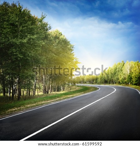 Empty curved road,blue sky and sun. - stock photo