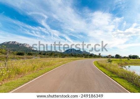 Empty curved road with blue sky - stock photo